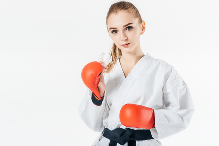 female karate fighter looking at camera with mouthguard and gloves isolated on white