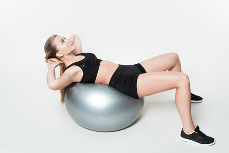 Attractive girl doing abs on fitness ball isolated on white Stock fotó