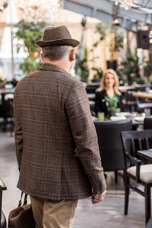 back view of man in stylish hat and jacket with woman sitting at table in restaurant Standard-Bild - 111819044