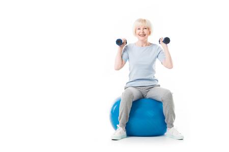 Smiling senior sportswoman with dumbbells sitting on fitness ball isolated on white