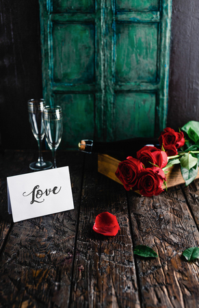 Love greeting card, red roses and champagne bottle with glasses on shabby wooden table, valentines day concept Stok Fotoğraf - 111819223