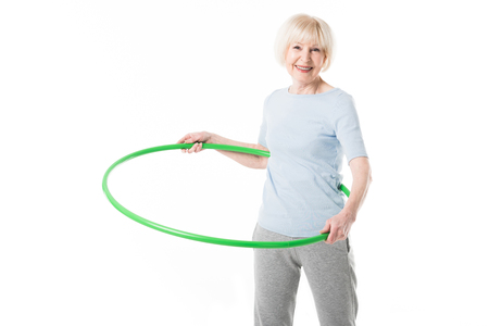 Senior sportswoman doing hula hoop exercise isolated on white