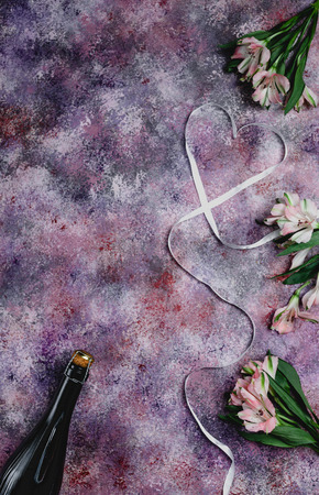 top view of champagne bottle, flowers and heart shaped ribbon on purple tabletop, valentines day concept Archivio Fotografico