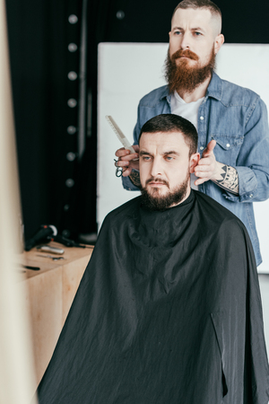 barber looking at client haircut in mirror at barbershop Stock Photo
