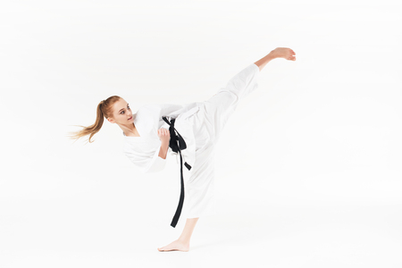 female karate fighter with black belt performing kick isolated on white