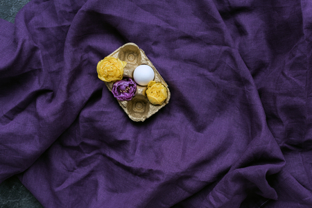 Chicken egg and flowers in carton on textile background 写真素材