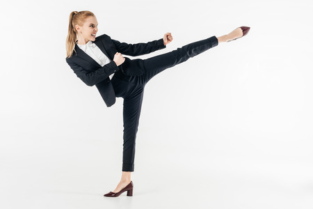 businesswoman performing karate kick in suit and high heels isolated on white Reklamní fotografie - 111819063