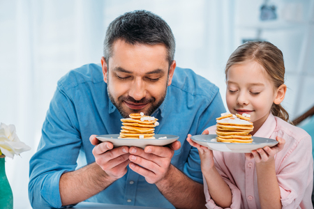 portrait of father and little daughter sniffing pancakes for breakfast at home