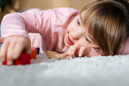 Kid with down syndrome playing with toy cubes while lying on a floor Stock fotó