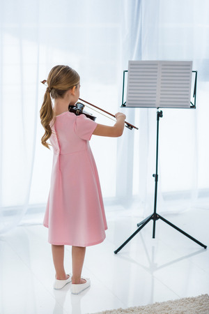 back view of little child in pink dress playing violin at home