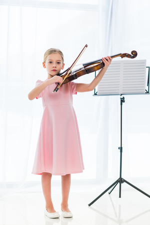 cute little child in pink dress playing violin at home Reklamní fotografie