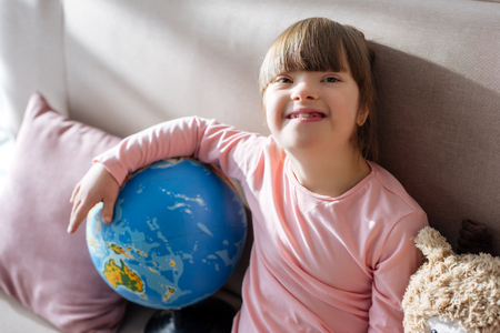 Smiling child with down syndrome holding globe Stock Photo