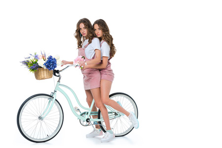 attractive young twins with bicycle and basket with flowers on white