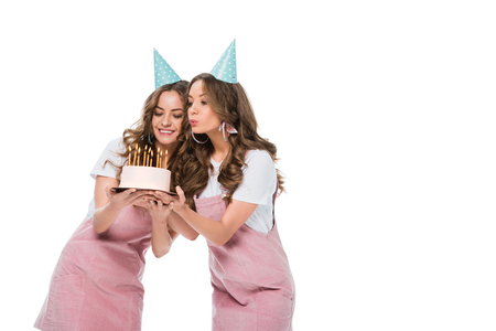 happy beautiful young twins blowing out candles on birthday cake isolated on white Banque d'images