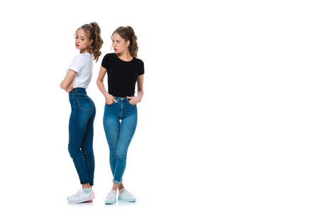 irritated young twin looking at sister isolated on white