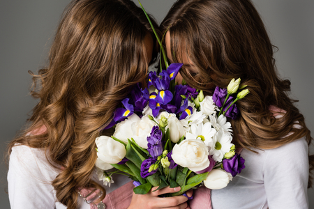 twins covering faces with bouquet isolated on grey Stock fotó