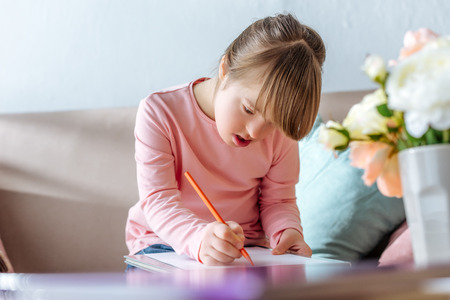 Child with down syndrome drawing with pencil while sitting on sofa