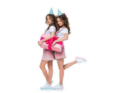 beautiful young twins holding one birthday present isolated on white