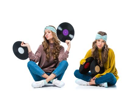 Jeunes jumeaux attrayants de style rétro assis avec des vinyles de 12 pouces isolés sur blanc Banque d'images