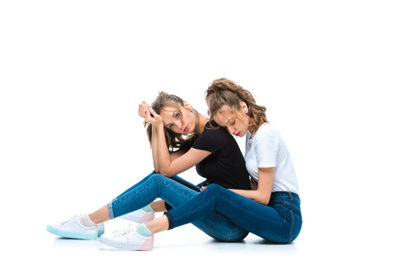 attractive young twins sitting of floor on white Фото со стока