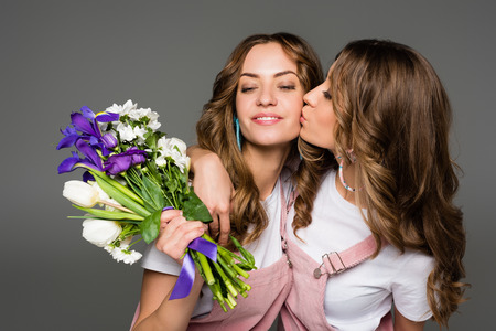attractive young twin kissing sister with bouquet isolated on grey