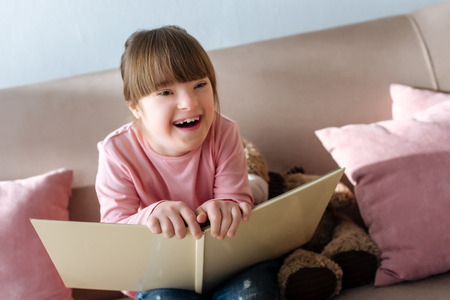 Kid with down syndrome holding book and laughing