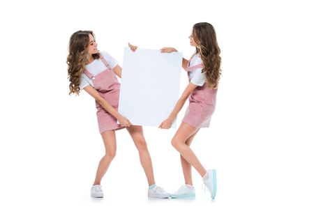 happy attractive young twins holding empty board isolated on white Zdjęcie Seryjne