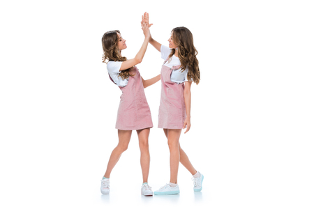 beautiful young twins giving high five isolated on white Stock Photo