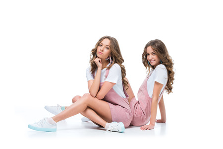 beautiful serious and smiling young twins sitting and looking at camera on white