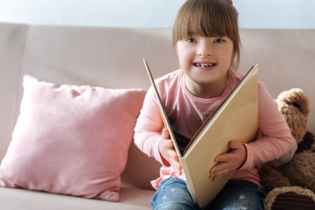 Laughing kid with down syndrome reading book