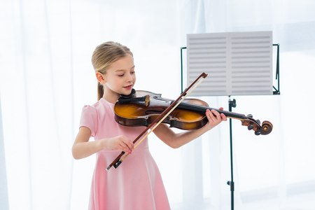 smiling little child in pink dress playing violin at home 版權商用圖片