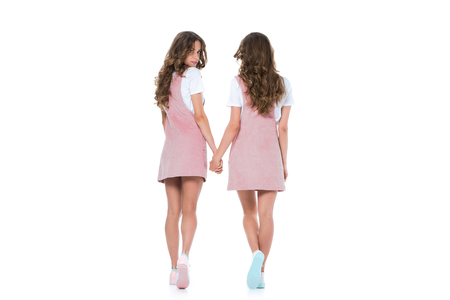 back view of young twins holding hands isolated on white