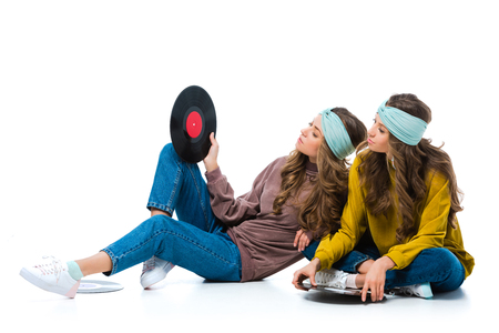 attractive retro styled young twins looking at vinyl record isolated on white