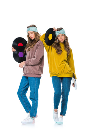 De jeunes jumeaux attrayants de style rétro avec des vinyles isolés sur blanc