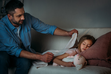 father covering sleeping daughter with blanket