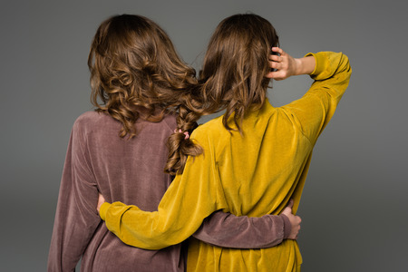 back view of twins hugging with hair in one braid isolated on grey