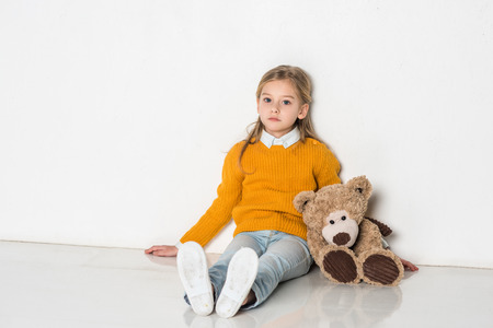 little kid with teddy bear looking at camera while sitting on floor Stock Photo