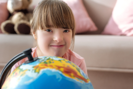 Kid with down syndrome looking at camera over globe Stock Photo