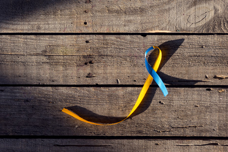 Blue and yellow ribbon as symbol of Down Syndrome Day on wooden background Stock fotó