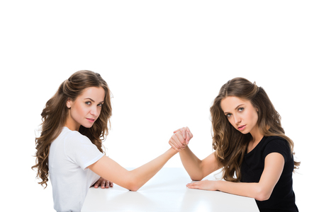 side view of young twins armwrestling at table and looking at camera isolated on white Stockfoto
