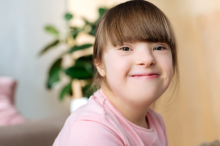 Portrait of smiling kid with down syndrome Фото со стока