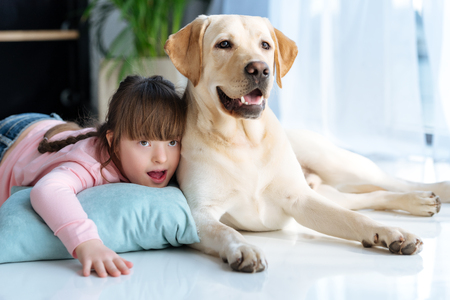 Kid with down syndrome lying on the floor next to Labrador retriever dog