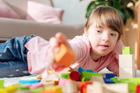 Niño con síndrome de down construyendo con cubos de juguete