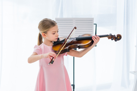 cute little child in pink dress playing violin at home 版權商用圖片