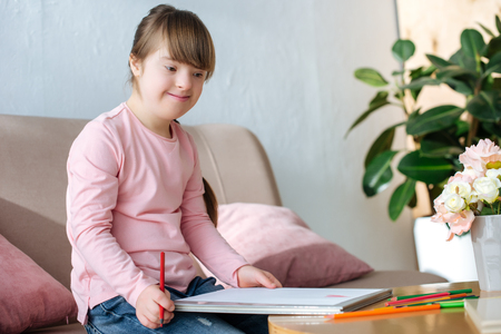 Child with down syndrome looking at drawing with colorful pencils