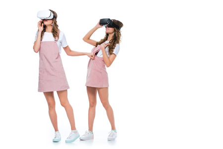 surprised twins watching something in virtual reality headsets isolated on white
