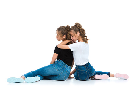 back view of attractive young twins hugging and sitting on floor on white