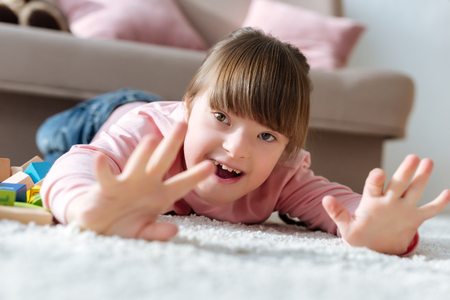 Happy child with down syndrome lying on floor in cozy room Фото со стока