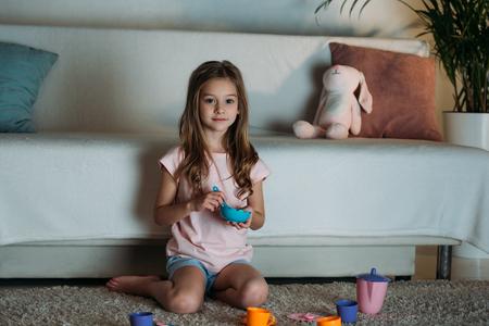 niño pequeño fingiendo que tiene una fiesta de té mientras está sentado en el piso en casa Foto de archivo