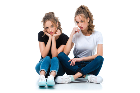 attractive young twins sitting on floor and looking at camera on white Imagens